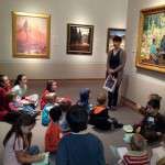 Childern looking at art and listening to a tour