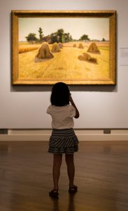 young girl looking at artwork