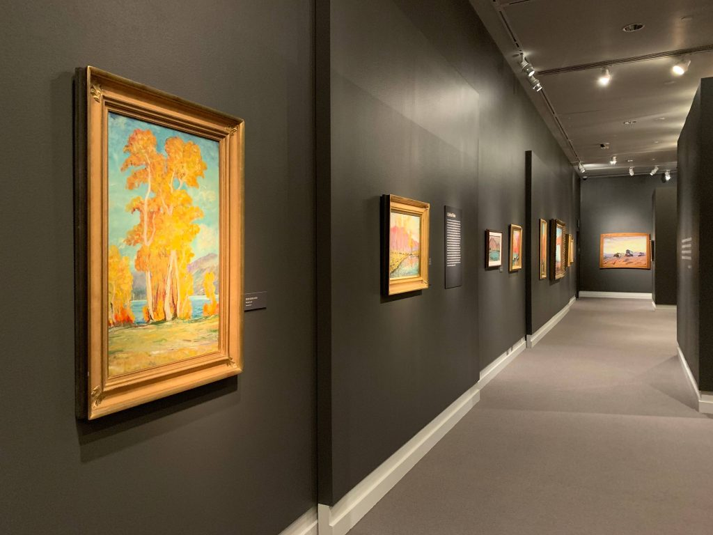 image of museum gallery with bright orange painting of tress in foreground, a corridor of paintings behind